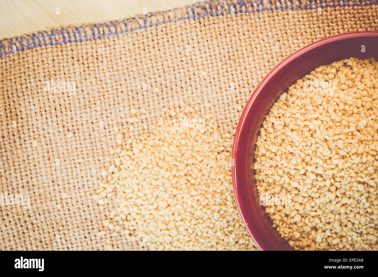 couscous grains in a brown porcelain bowl on a burlap surface - Stock Image