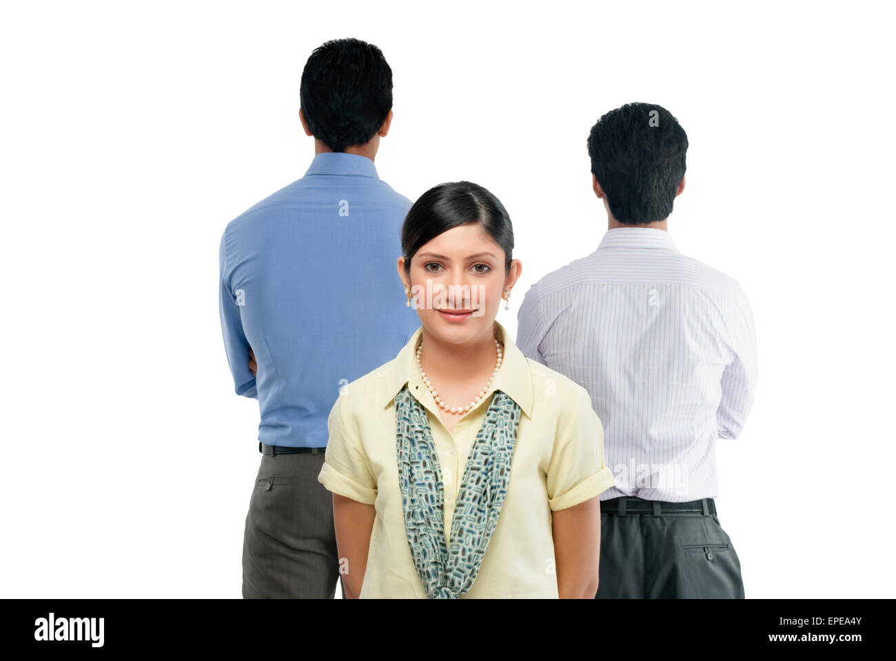 One businesswoman looking in front and two businessmen standing with their backs in front - Stock Image