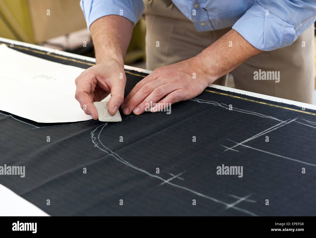 Tailor or designer using chalk to mark a pattern on to a length of fabric - Stock Image