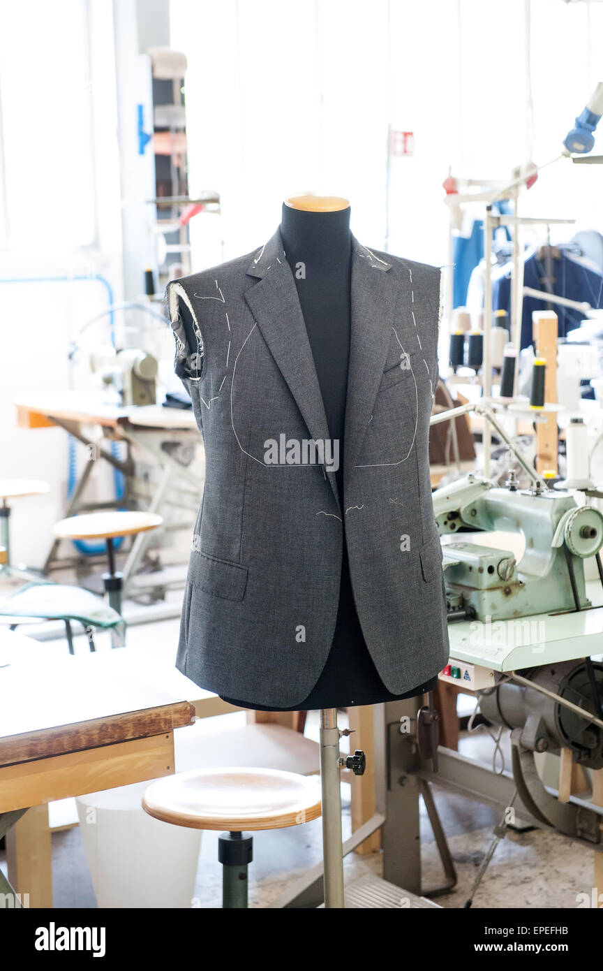 Working on a handmade jacket displayed on a mannequin ready for the fitting of the sleeves in the interior of a - Stock Image