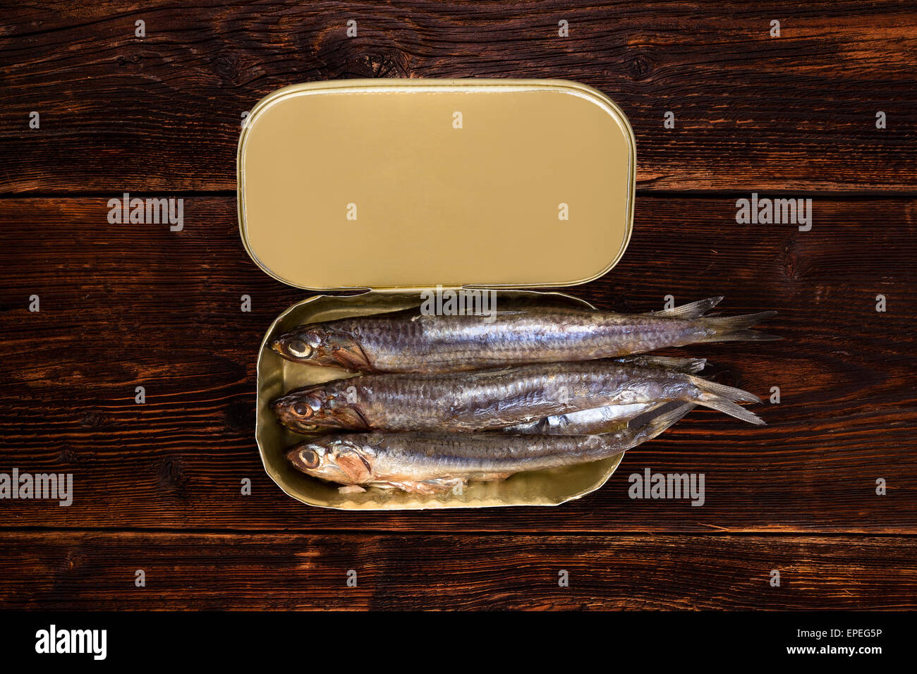 Sardines in can on old wooden textured background with lemon piece. Culinary healthy fish eating. - Stock Image