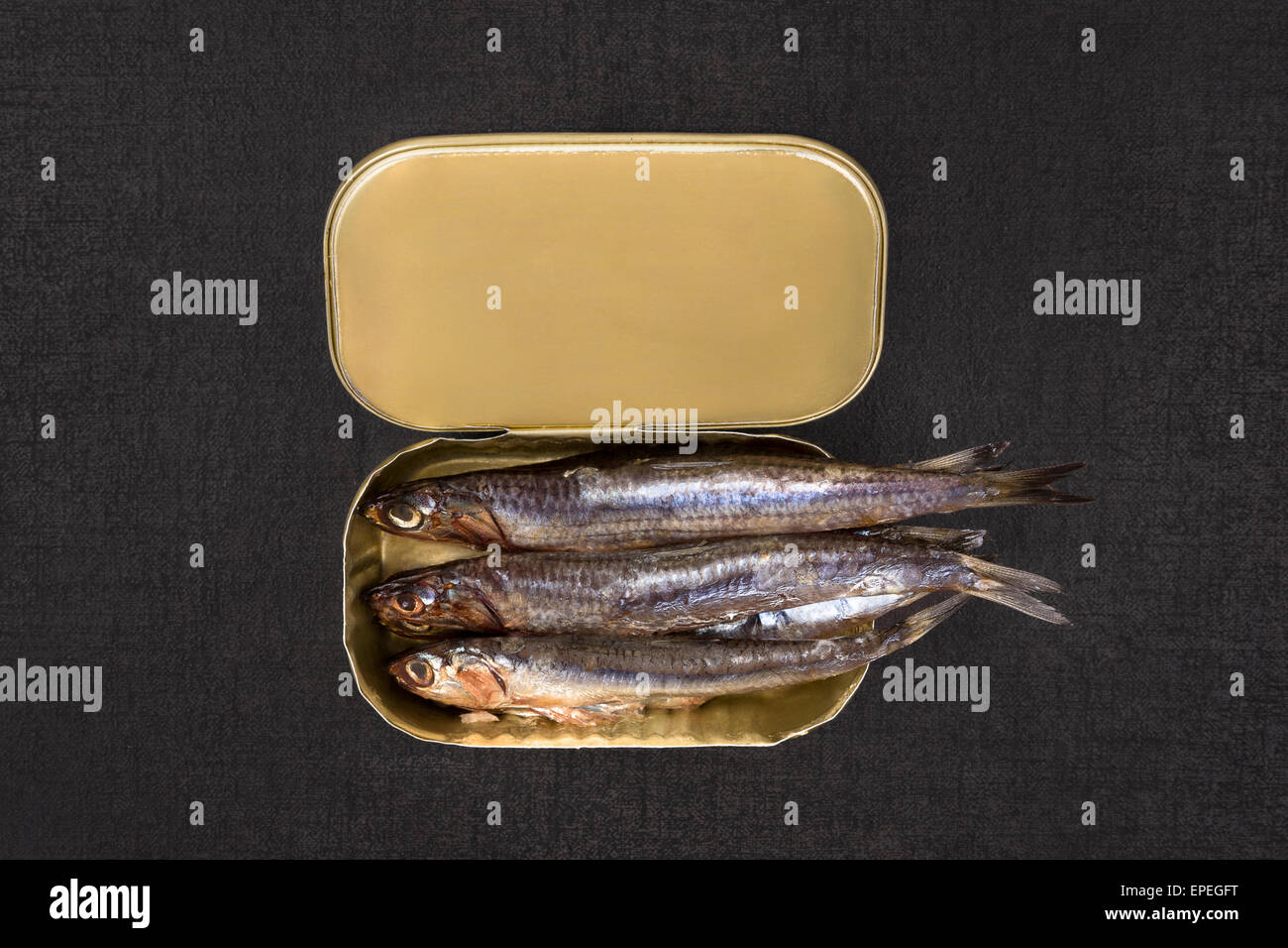 Open can with sardines isolated on black textured background, top view. Culinary seafood eating. - Stock Image