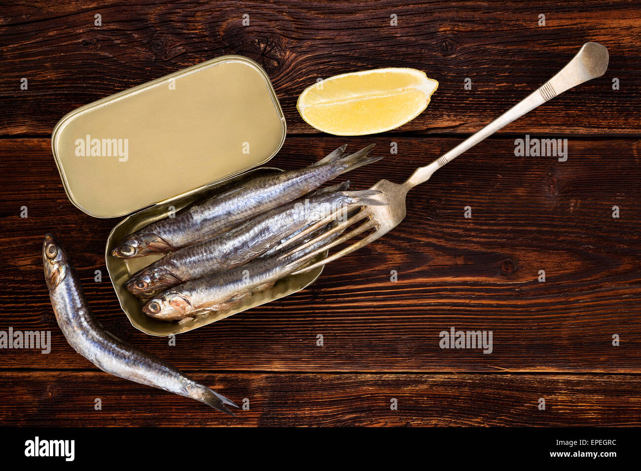 Sardines on old wooden textured background with lemon piece. Culinary healthy fish eating. - Stock Image