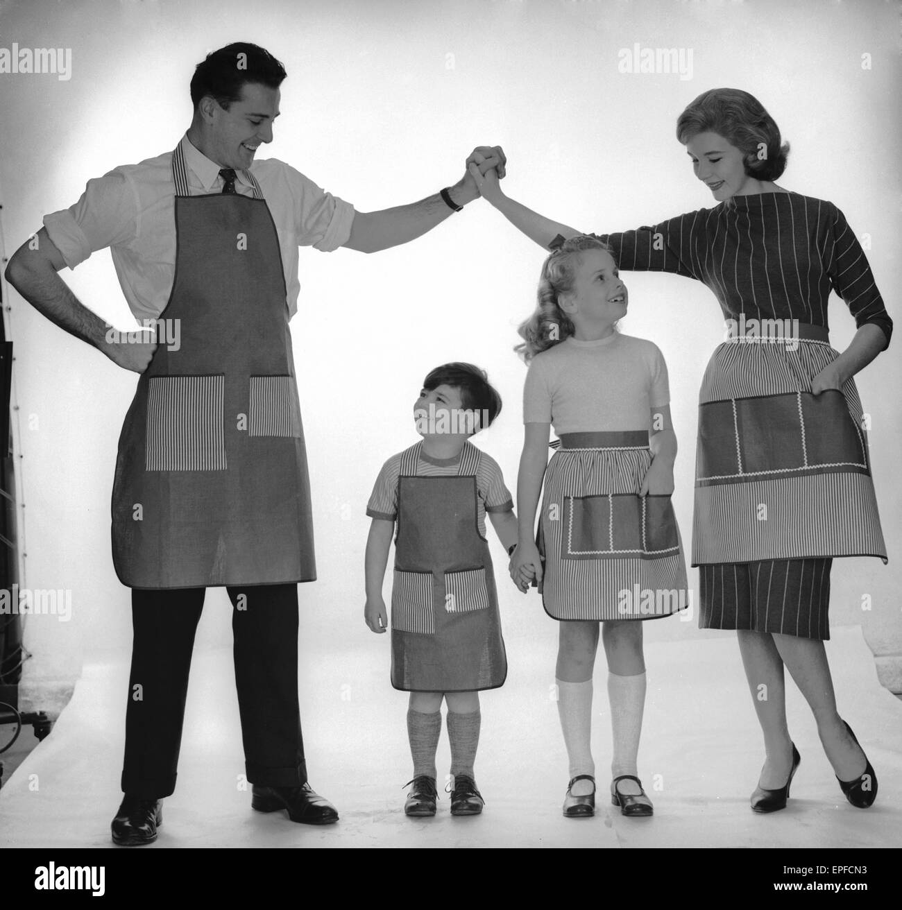 Family modelling a set of aprons for Reveille. 2nd December 1957 Stock Photo