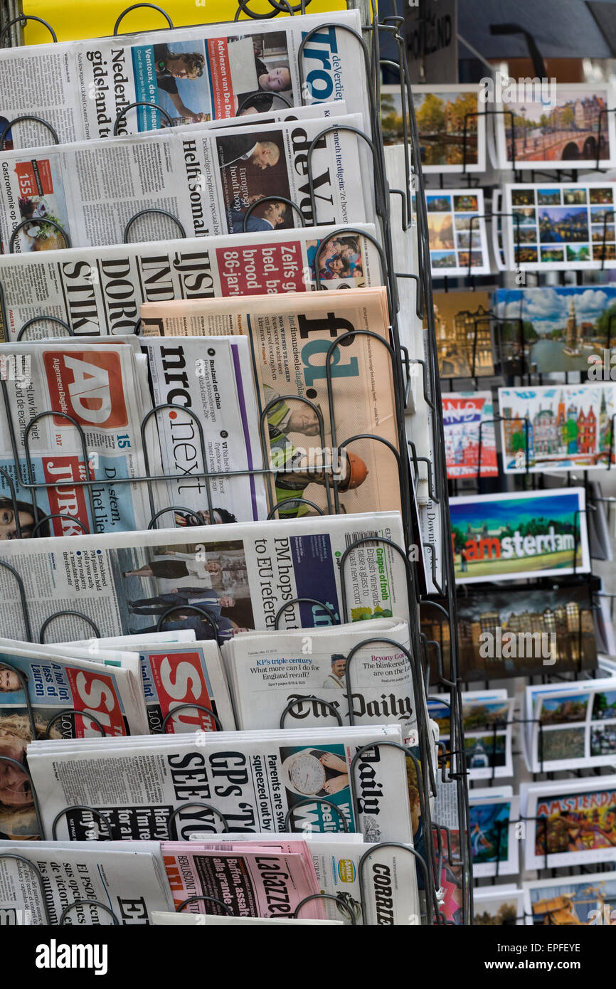 International Newspapers and post cards on a stand - Stock Image