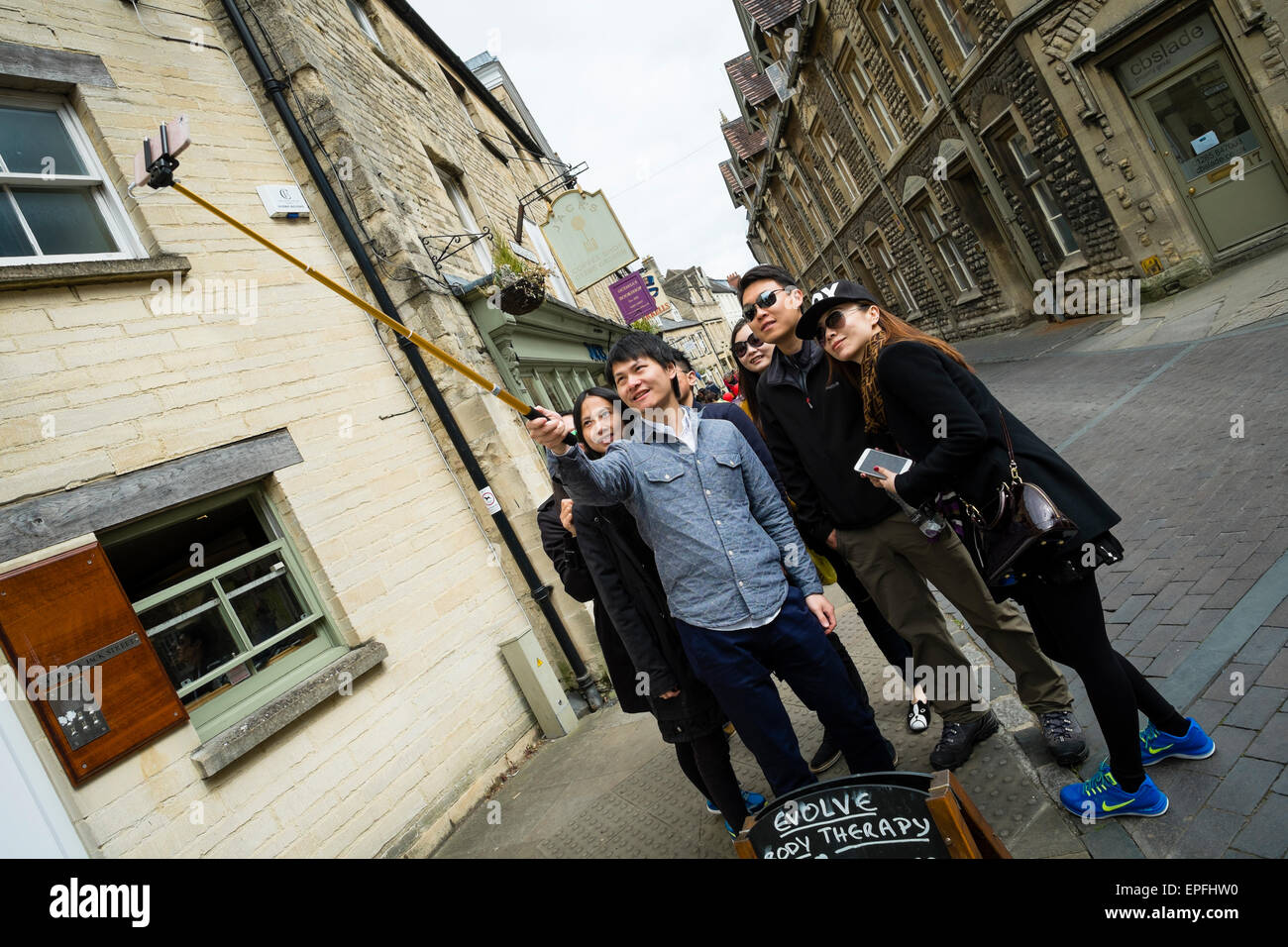 A group of young happy smiling Chinese tourists taking a selfie on a stick in the centre of Cirencester, Gloucestershire, Stock Photo