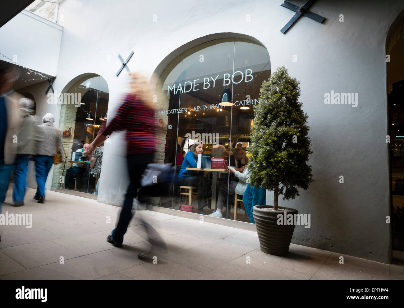 Exterior: people walking past  Made by Bob cafe restaurant and delicatessen, Cirencester, Gloucestershire, England - Stock Image