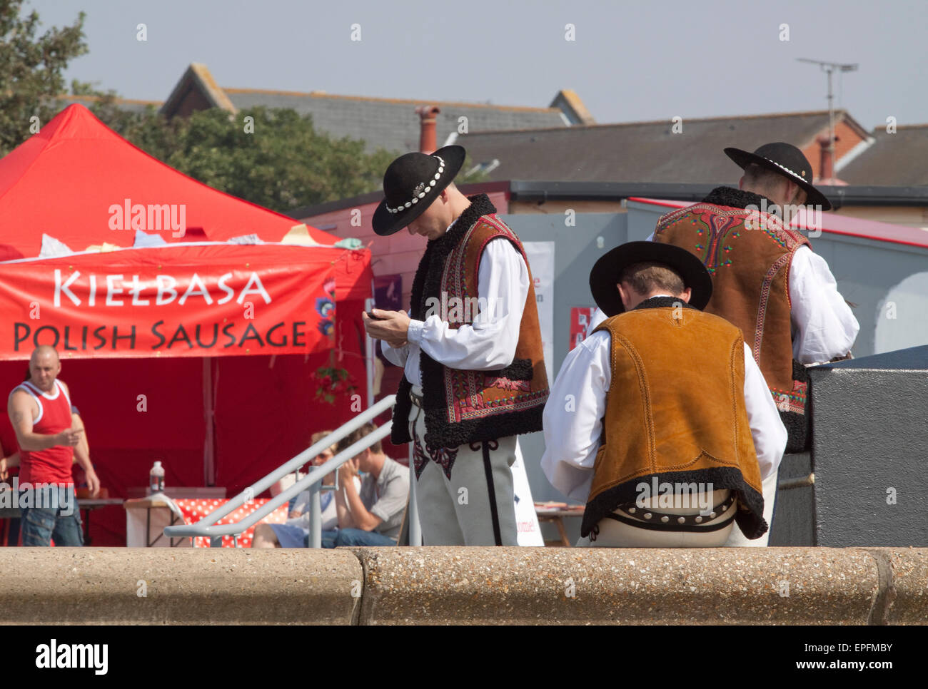 Three young men in traditional Polish costume check their phones at the 2011 Polish Arts Festival in Southend - Stock Image