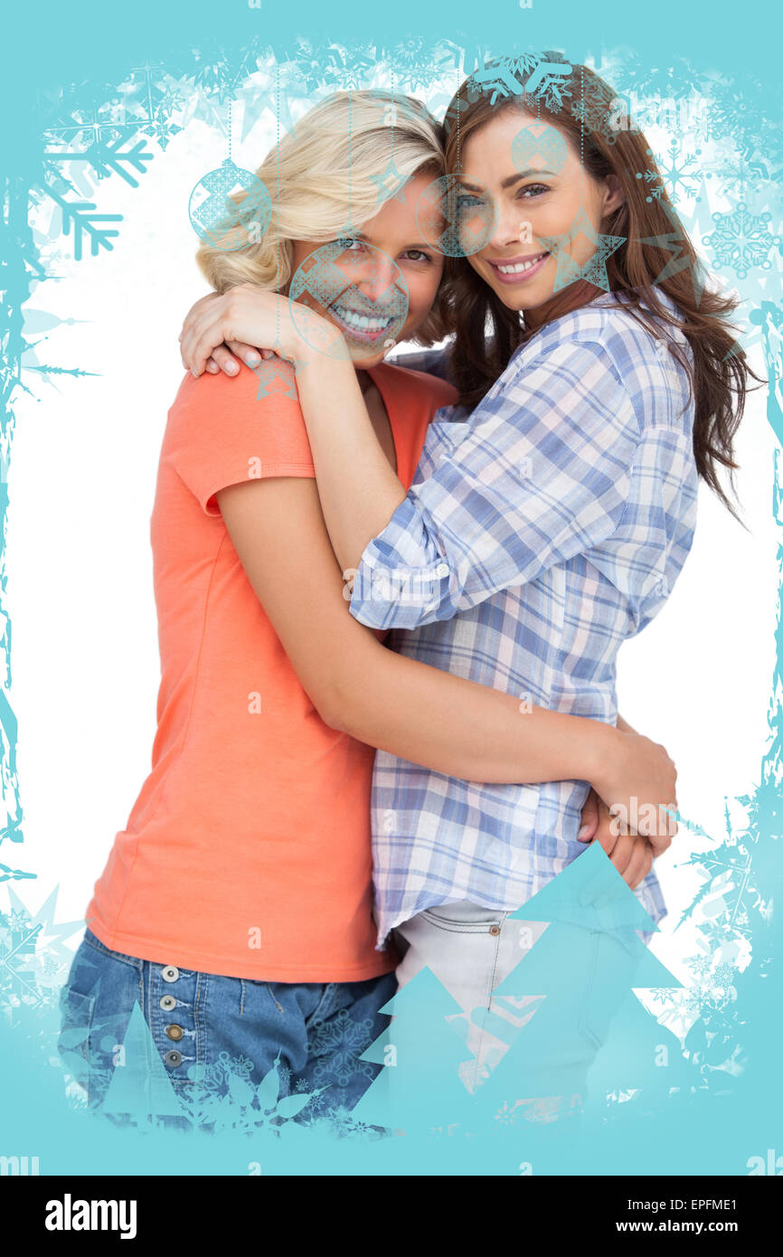Composite image of two cute friends looking at the camera and hugging - Stock Image