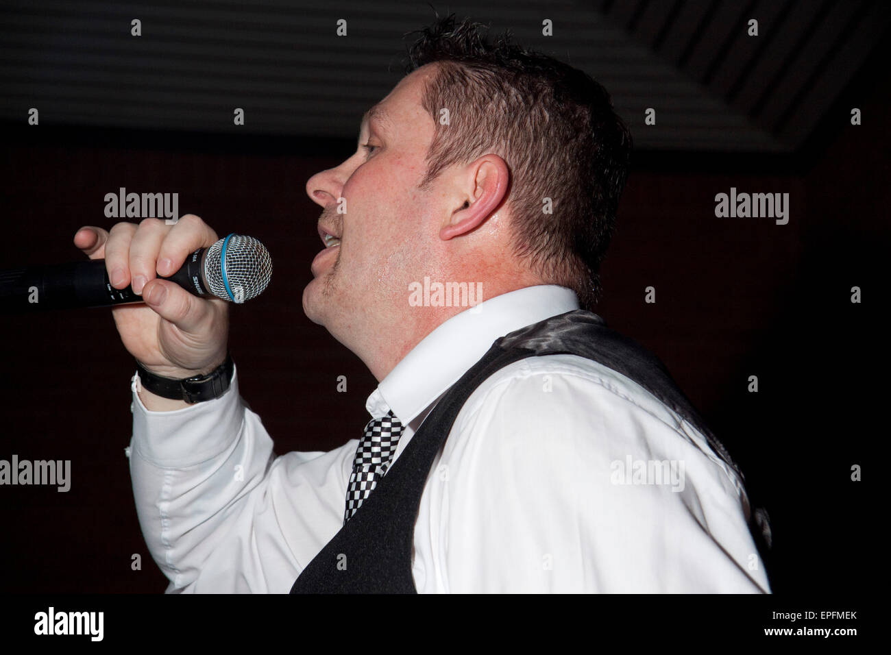 Man in white shirt, waistcoat, and black and white tie speaks/sings in to microphone - Stock Image