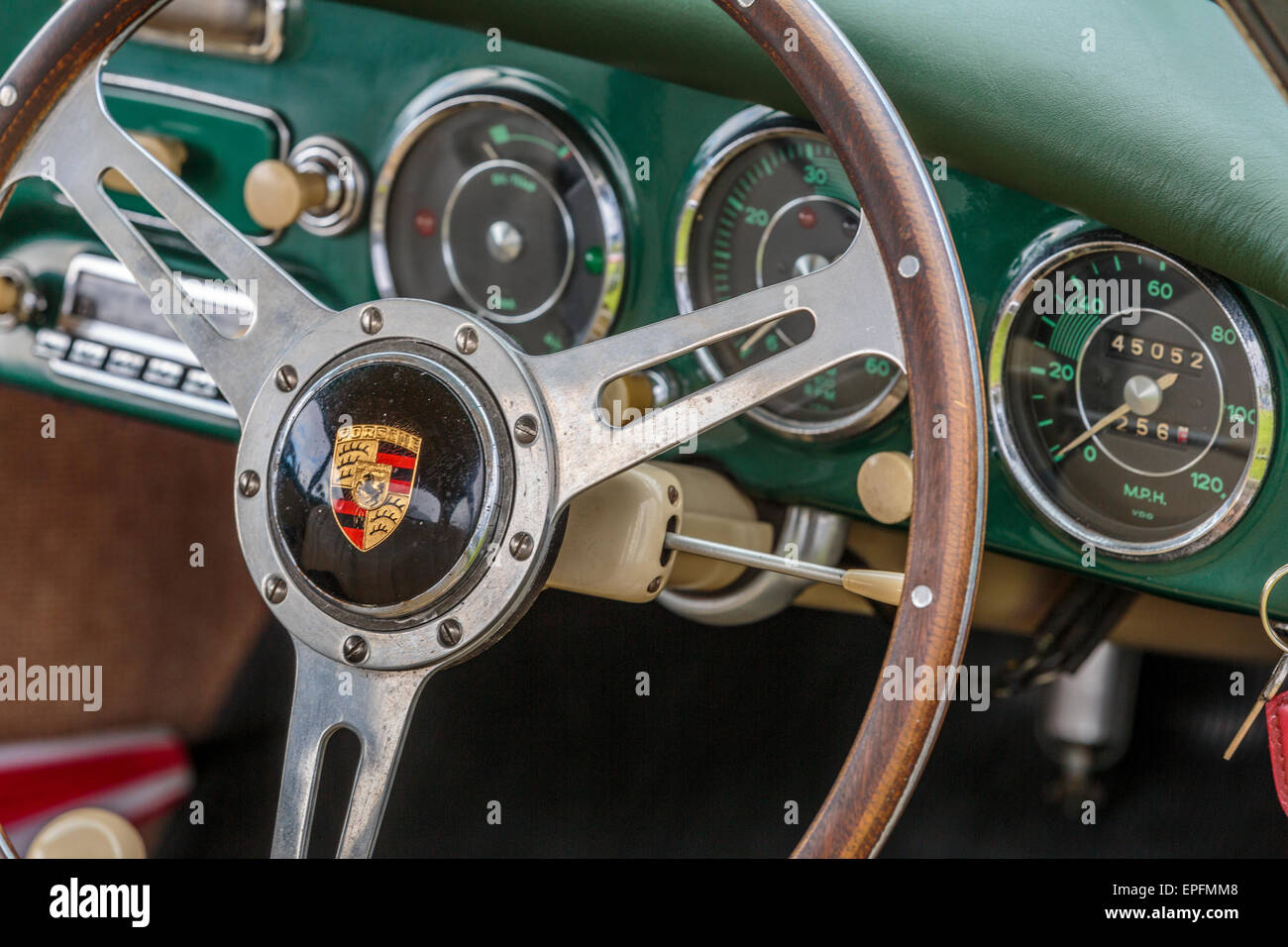An image of A Porsche 356 steering wheel with green leather dashboard trim - Stock Image