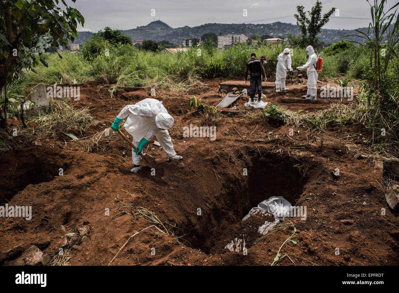 A burial team fills in the grave of a suspected Ebola victim in Kingtom Cemetery.Ebola is now rampant within the - Stock Image