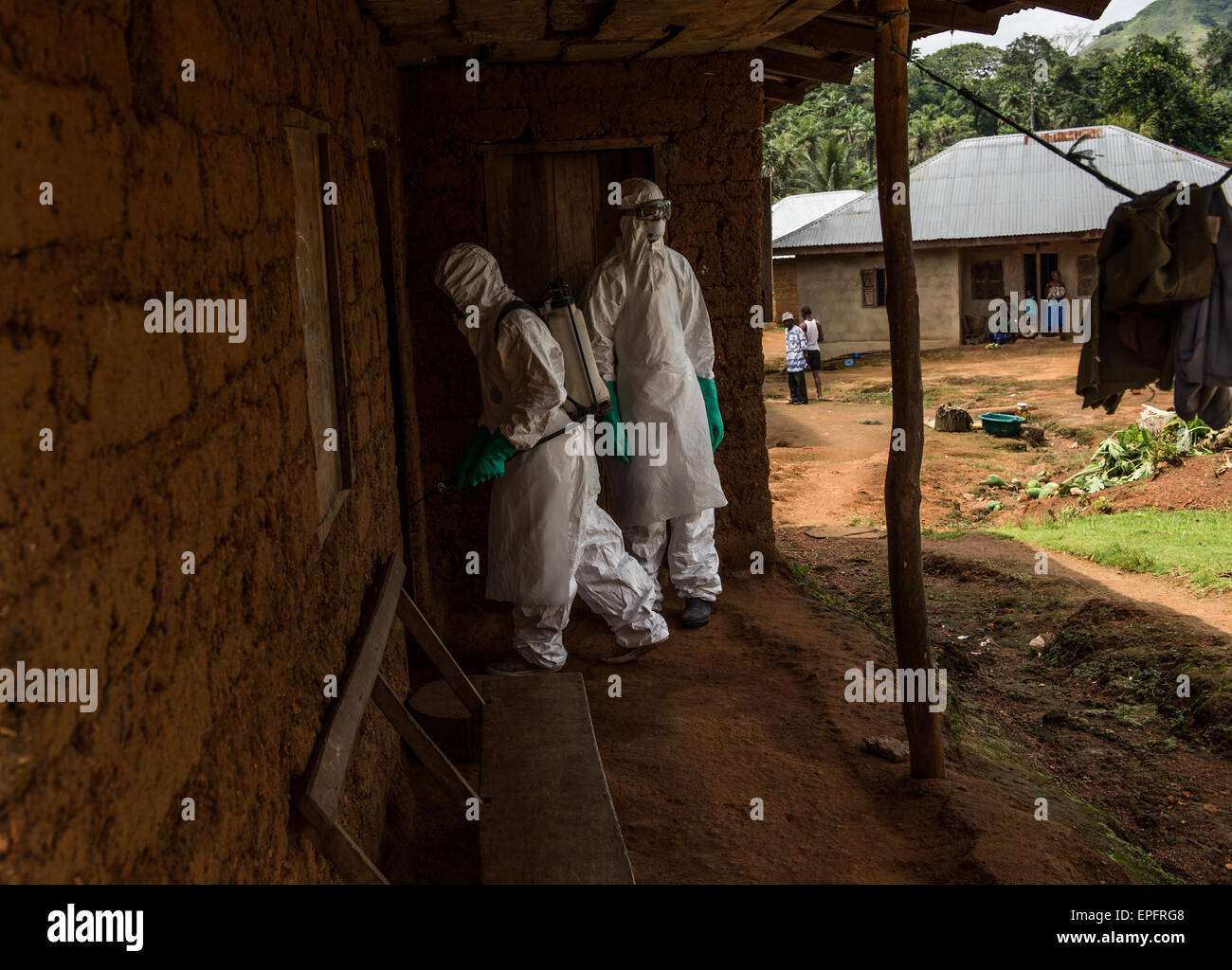 Members of a burial team enter the home of the deceased in Komende Luyama village. Eastern Sierra Leone was a hot - Stock Image