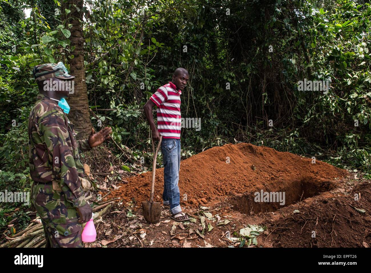 A soldier looks on as a man stands by a grave where a suspected Ebola victim is about to be buried. Eastern Sierra - Stock Image