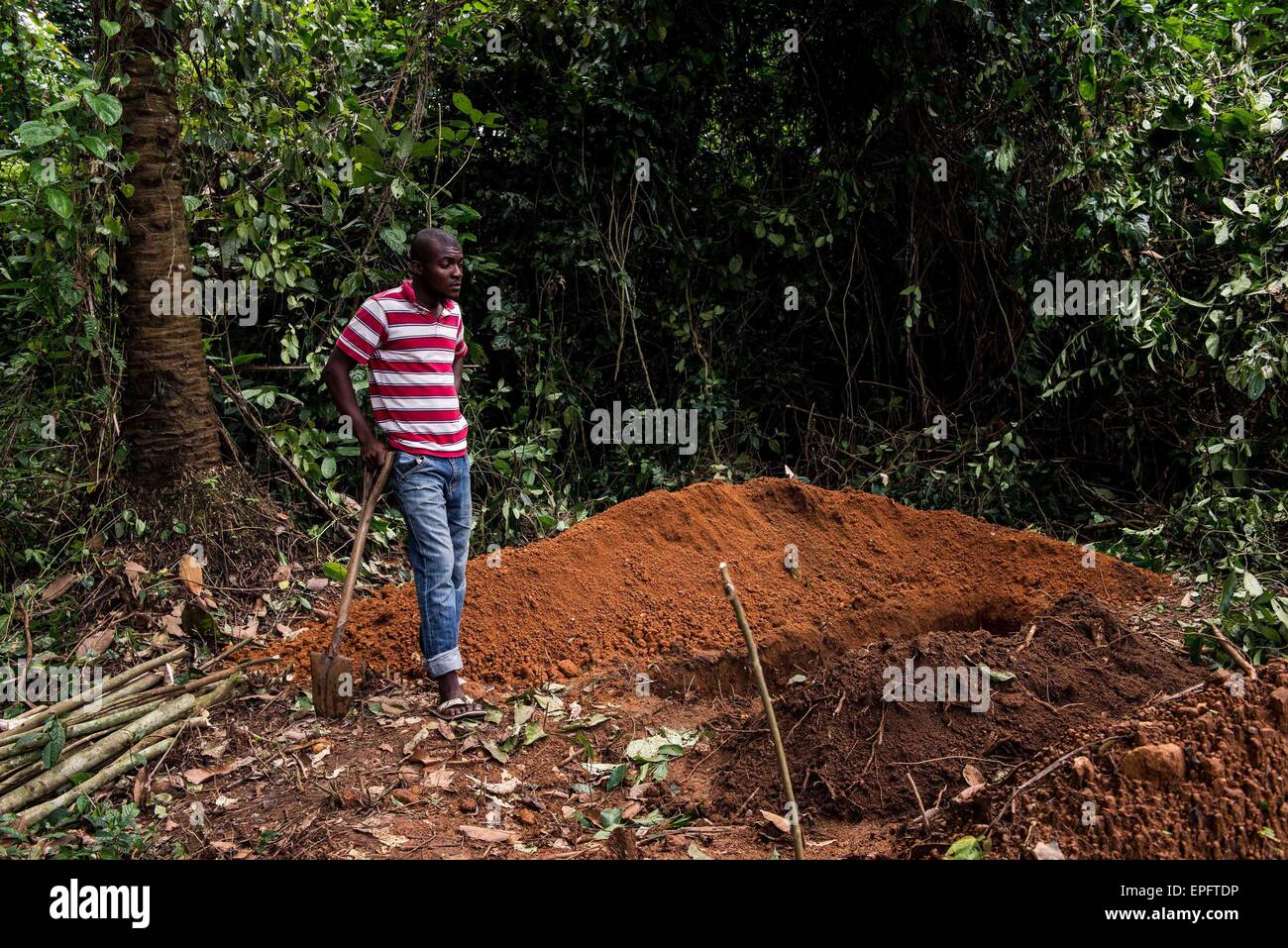 A man stands by a grave where a suspected Ebola victim is about to be buried. Eastern Sierra Leone was a hot spot - Stock Image