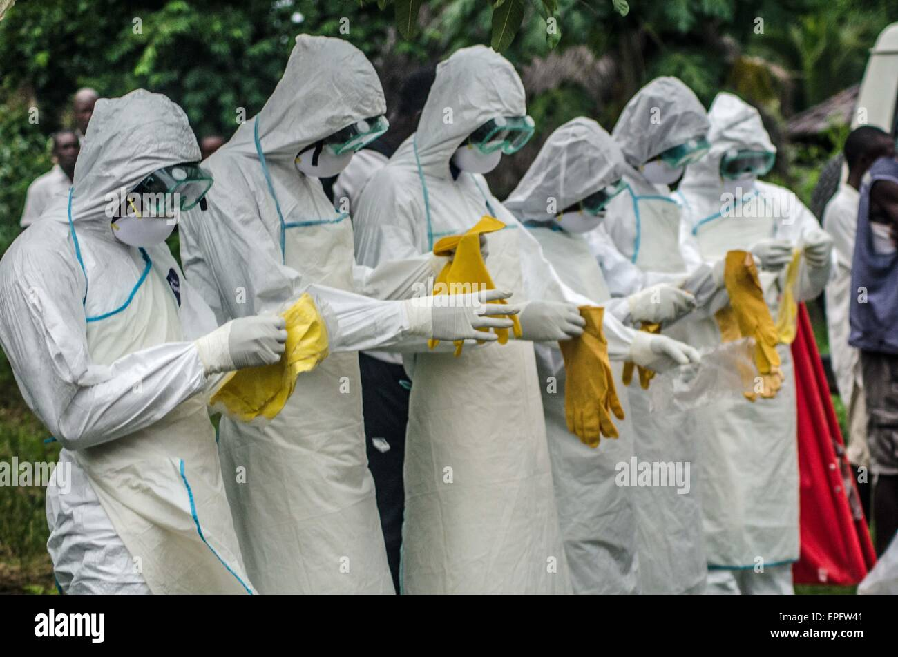 A burial team puts on PPE before collecting a suspected Ebola victim. - Stock Image