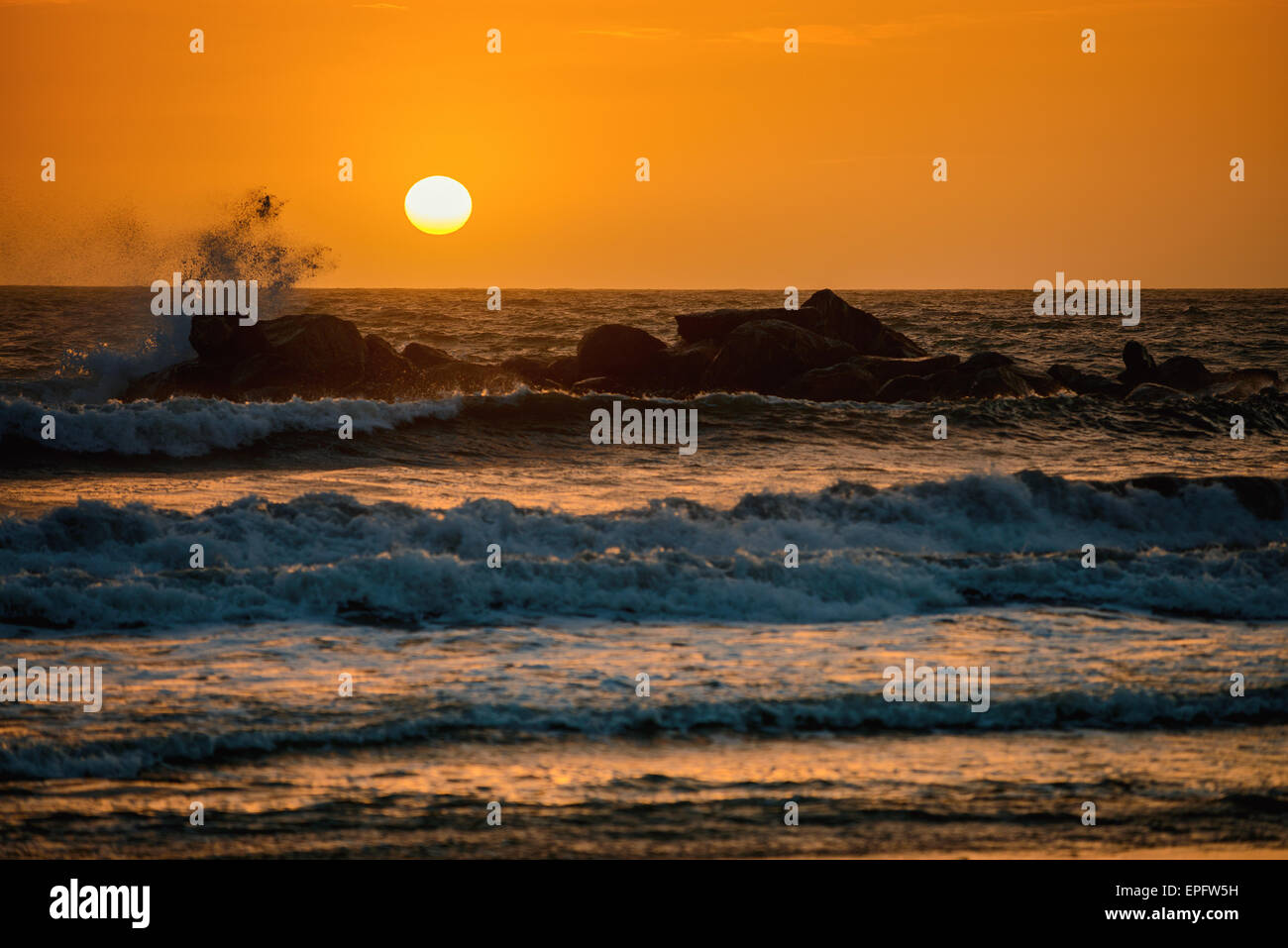 Sunset above the ocean from the rocky beach. Warm tones effect. - Stock Image