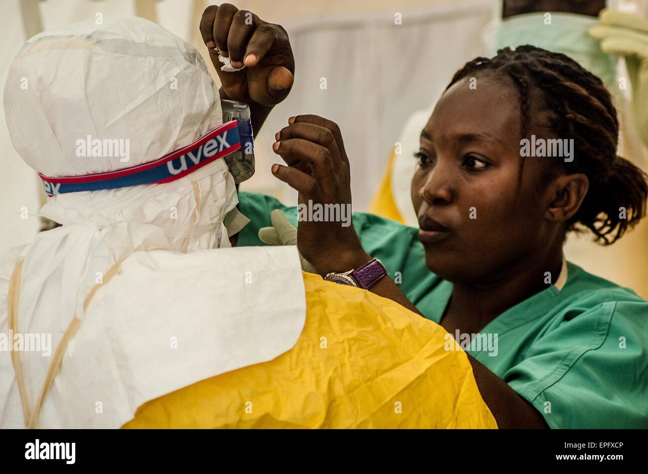 A nurse helps another staff member to put on PPE at a MSF Ebola treatment center in kailahun, Sierra Leone. - Stock Image