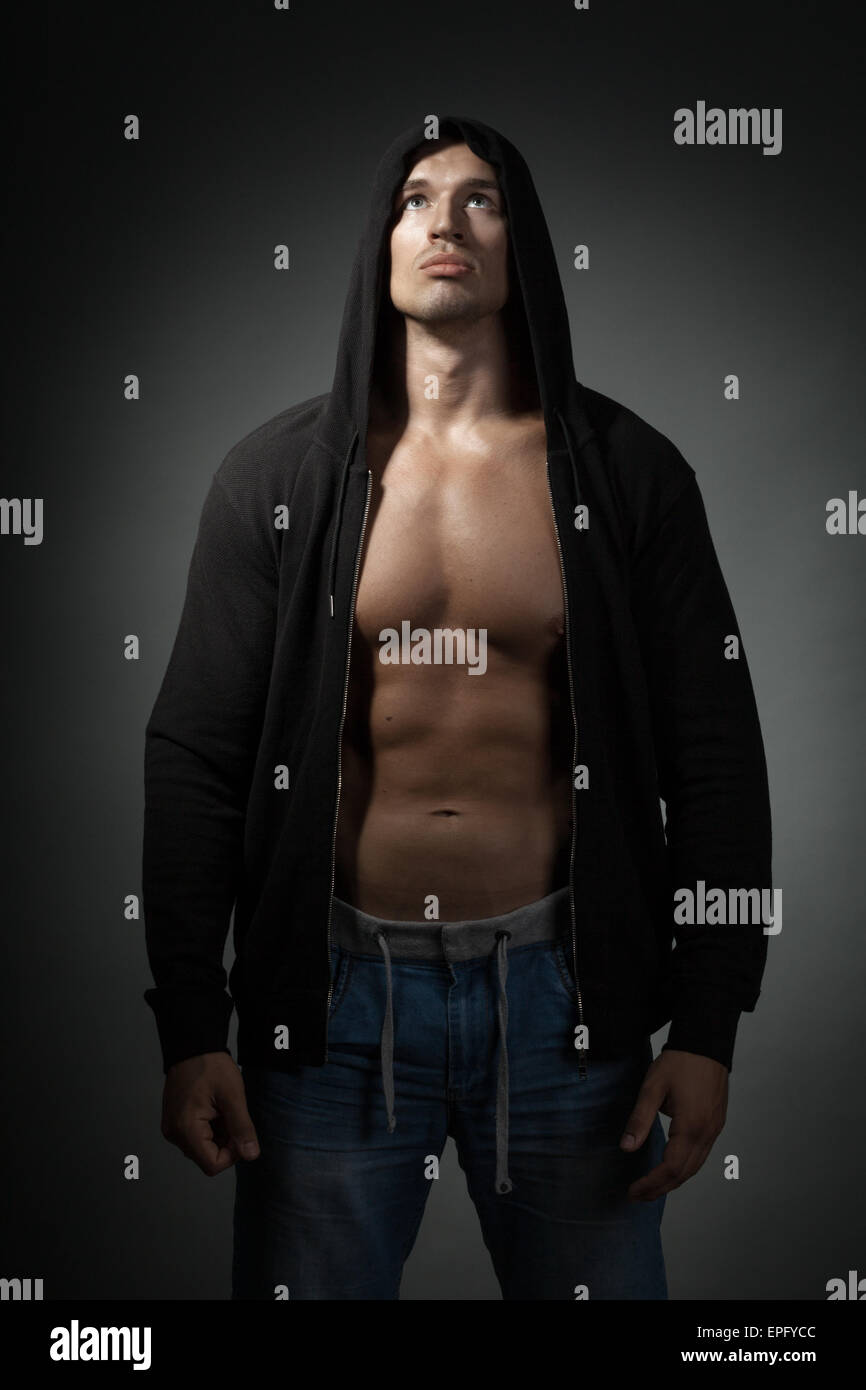 strong man wearing black hoodie isolated on dark - Stock Image