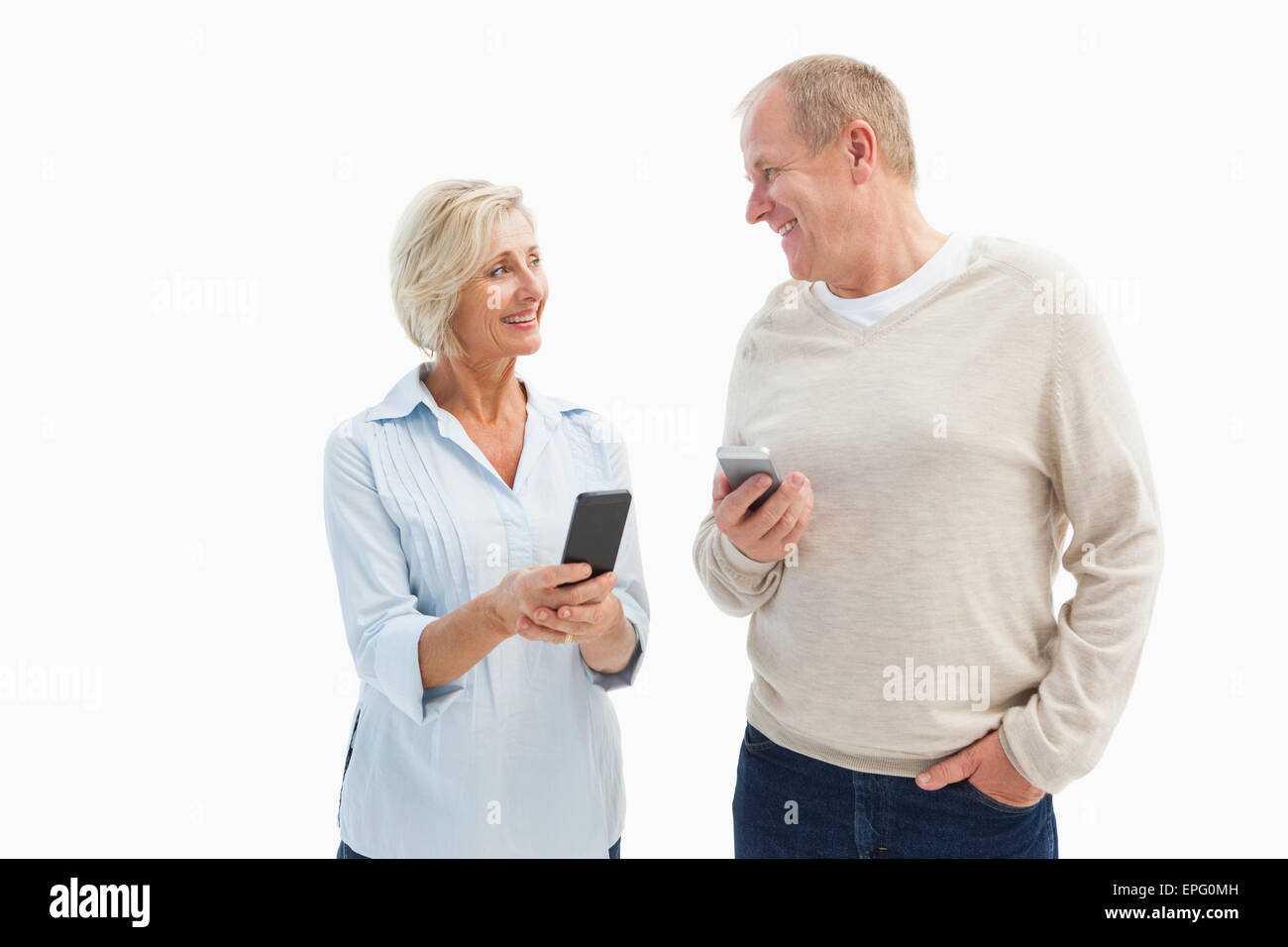Happy mature couple using their smartphones - Stock Image