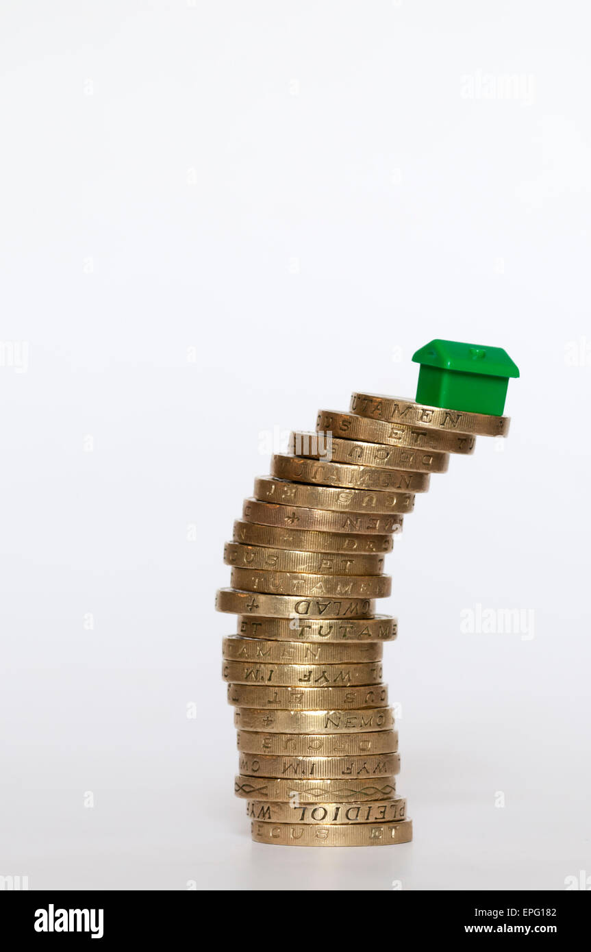 A small plastic model green house balanced on top of a leaning pile of pound coins.  Housing finance concept. - Stock Image