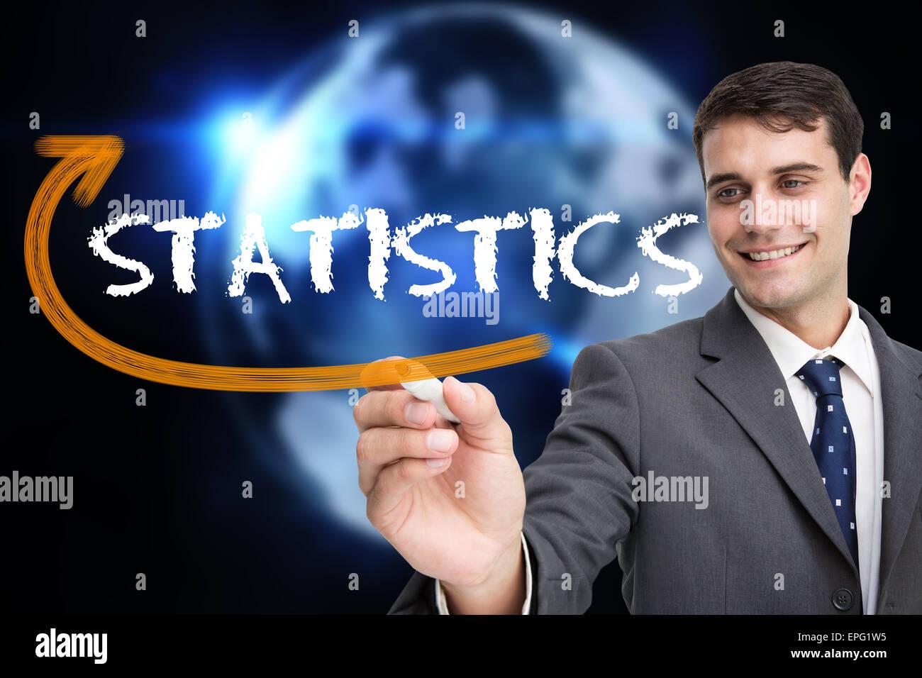 Businessman writing the word statistics Stock Photo