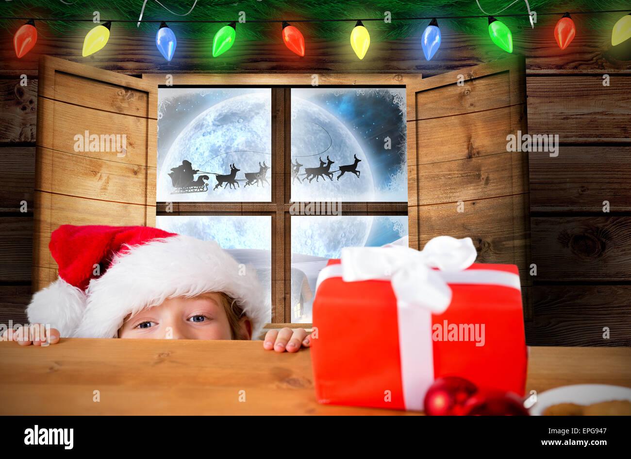 Composite image of festive boy peeking over table - Stock Image