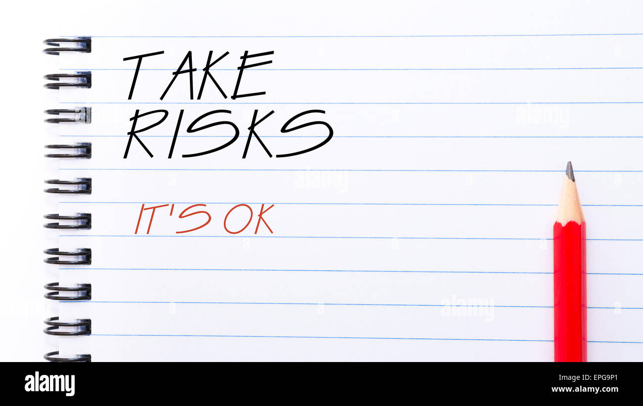 Take Risks, It Is OK  Text written on notebook page, red pencil on the right. Motivational Concept image - Stock Image