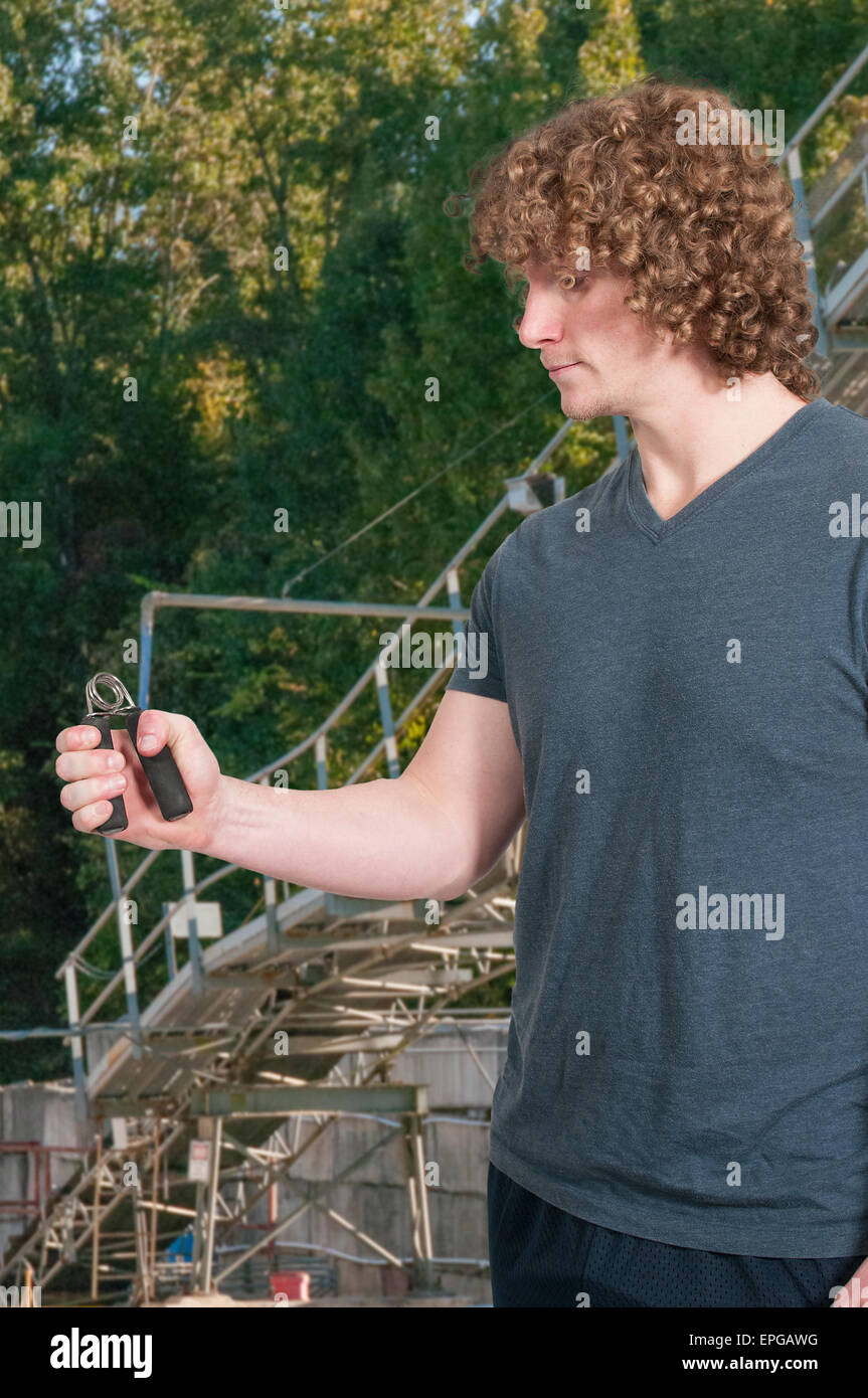 Man with hand grip exerciser - Stock Image