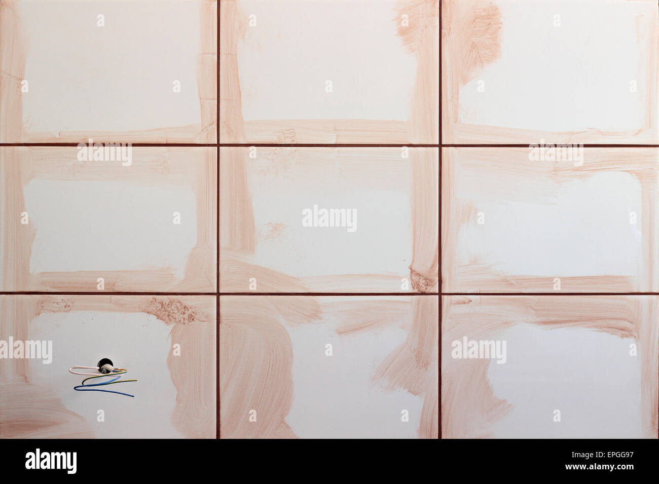 Jointing of a white tile cement of cream color. - Stock Image