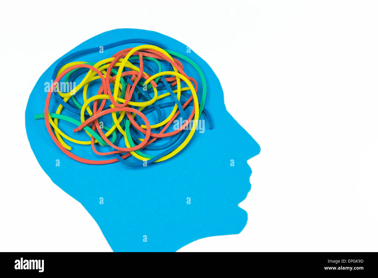 Blue shape of a human head with tangled colored elastic bands , concept for complexity of the human mind - Stock Image