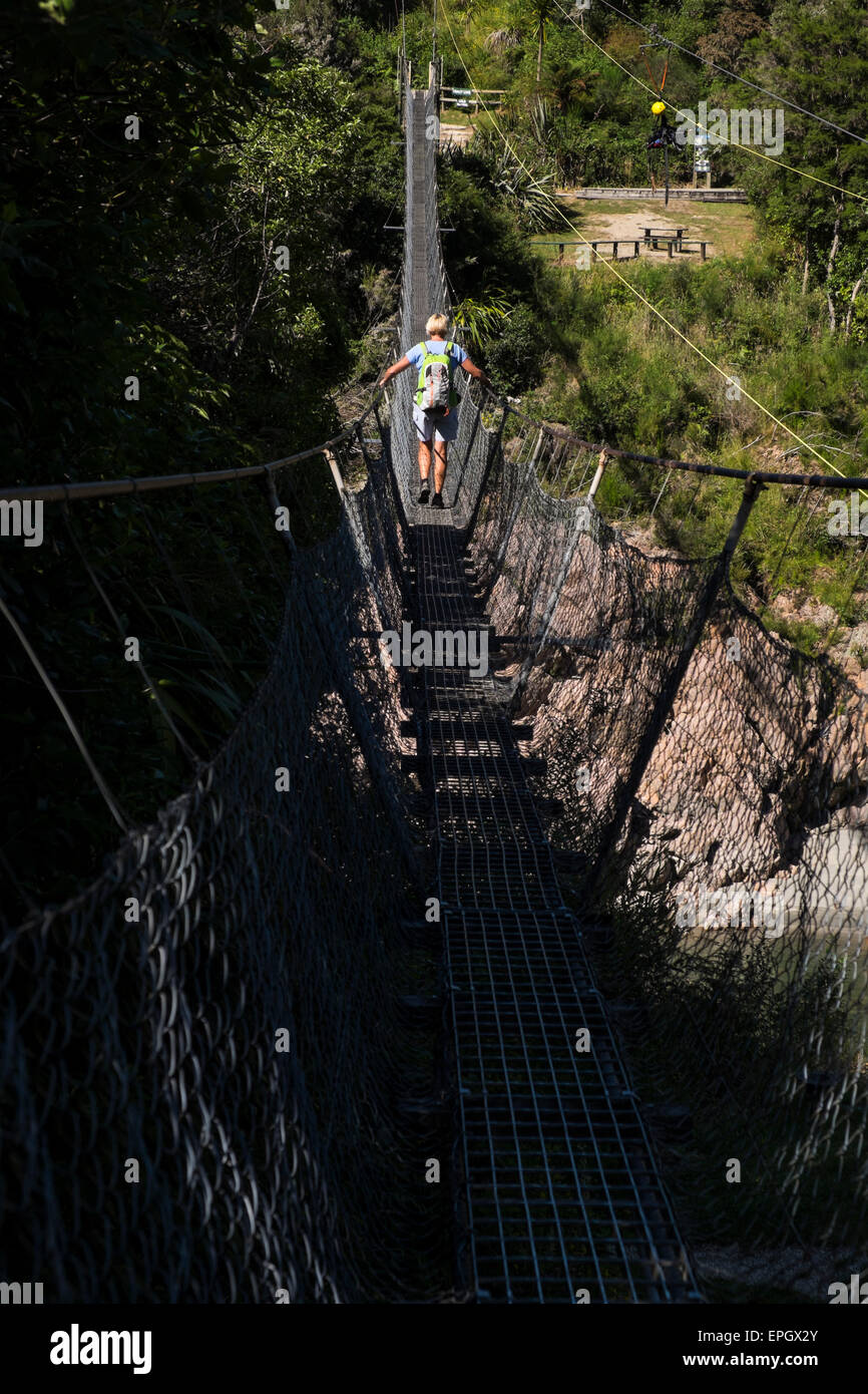 Woman crossing Buller Gorge swingbridge, New Zealand. - Stock Image