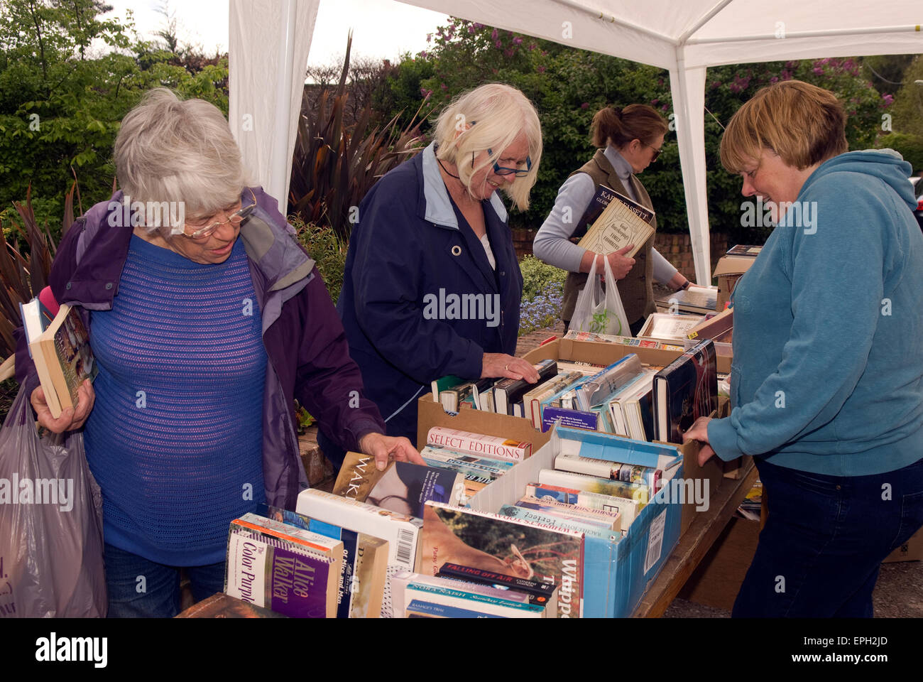 Women perusing the bookstall at a May Fayre, Oakhanger, Hampshire, UK. - Stock Image