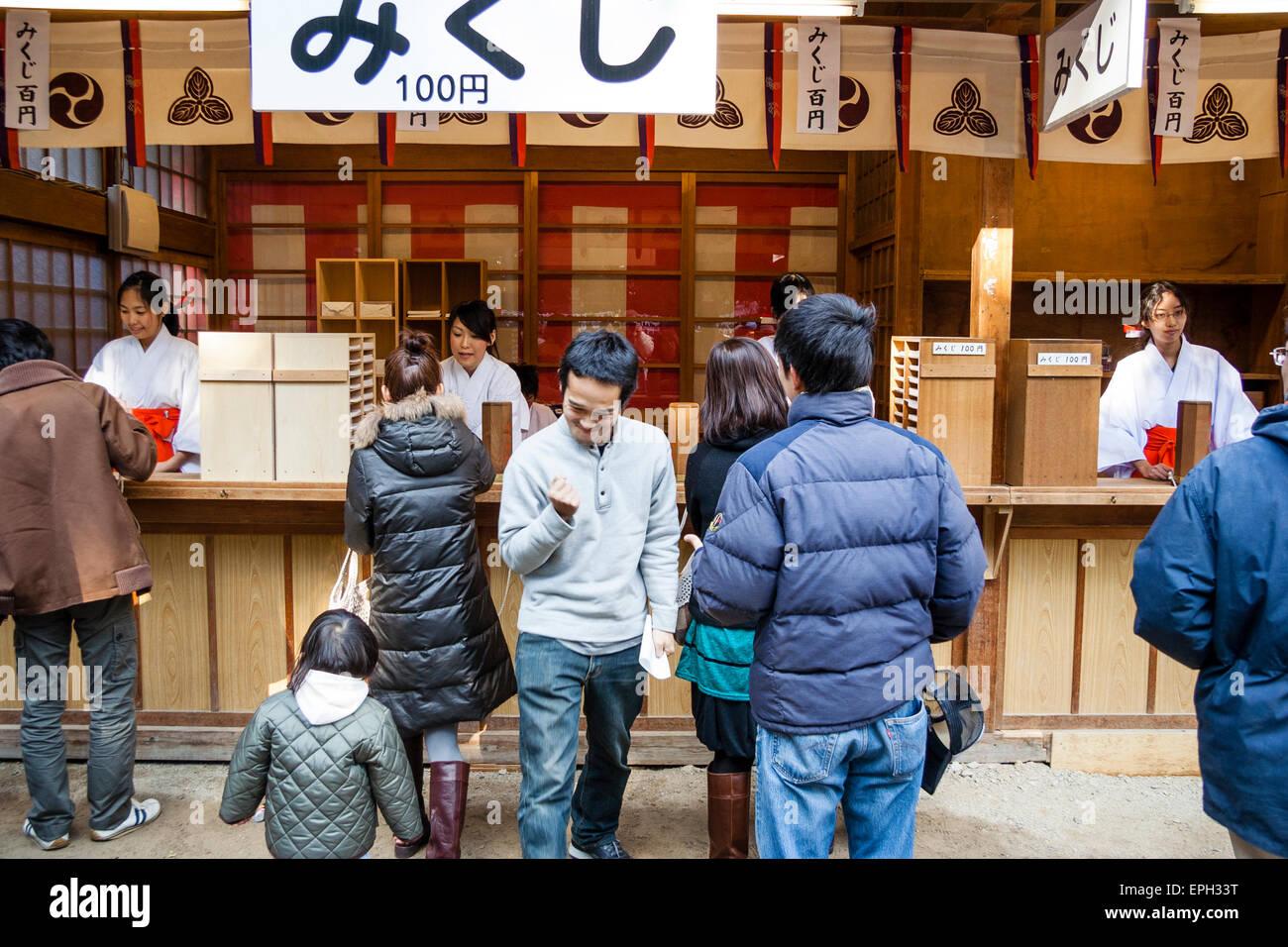 Japan, Nishinomiya shrine. New Year. People buying omikuji, during at hatsumode. One man, clenching fist, ecstatic, - Stock Image