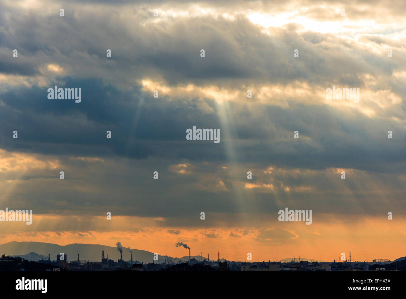 Japan, Himeji. Sunburst through thick stomry heavy clouds over city and industry with smoking factory chimneys, - Stock Image