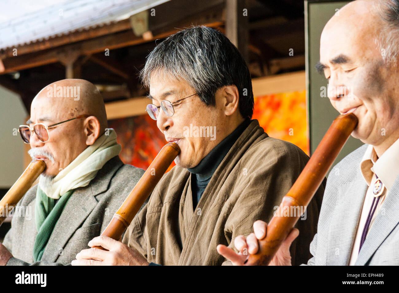 Japan, Nishinomiya, Koshiki-wa shrine. Row of elderly men in suits and jackets kneeling on stage playing flute recital. - Stock Image