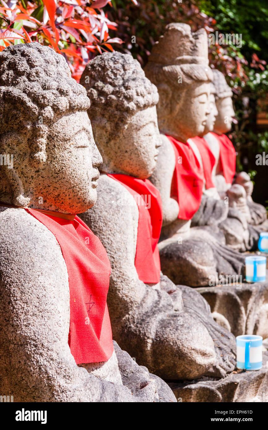 Japan, Kobe, Suma-Dera temple. Row of five sitting stone Jizo dosatsu statues with red bibs on. View along. - Stock Image