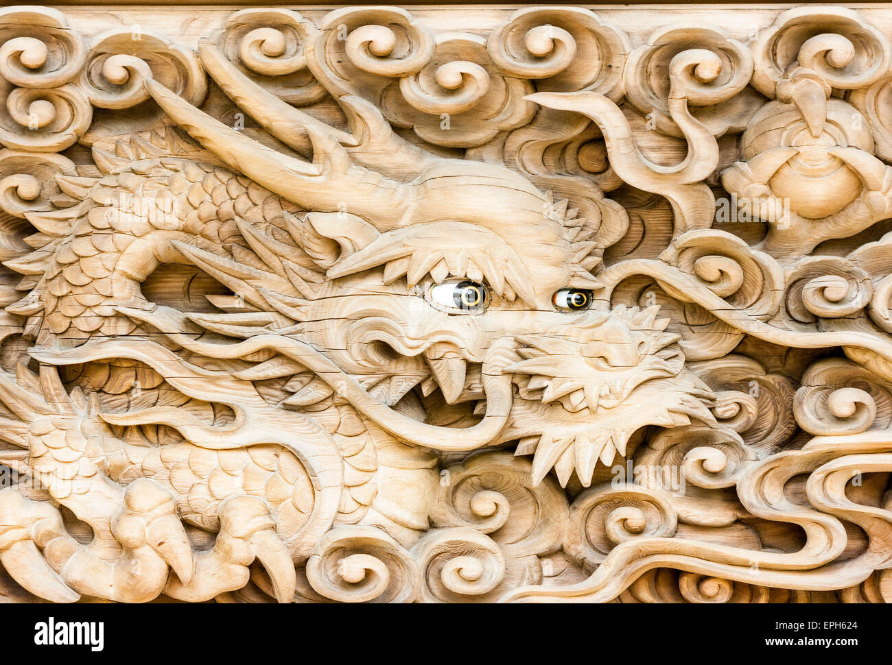 Japan, Kobe, Suma-dera temple. Buddhist Kondo Hall, roof detail. Wooden carved face of dragon with inlaid eyes. - Stock Image