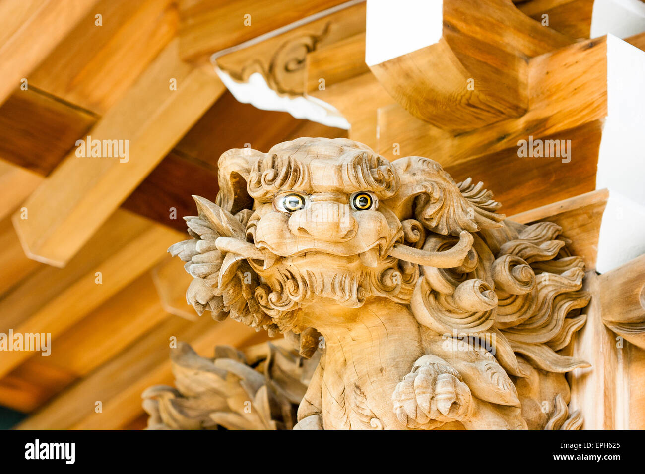 Japan, Kobe, Suma-dera temple. Buddhist Kondo Hall, roof detail. Wooden carved face of dog like dragon with inlaid - Stock Image