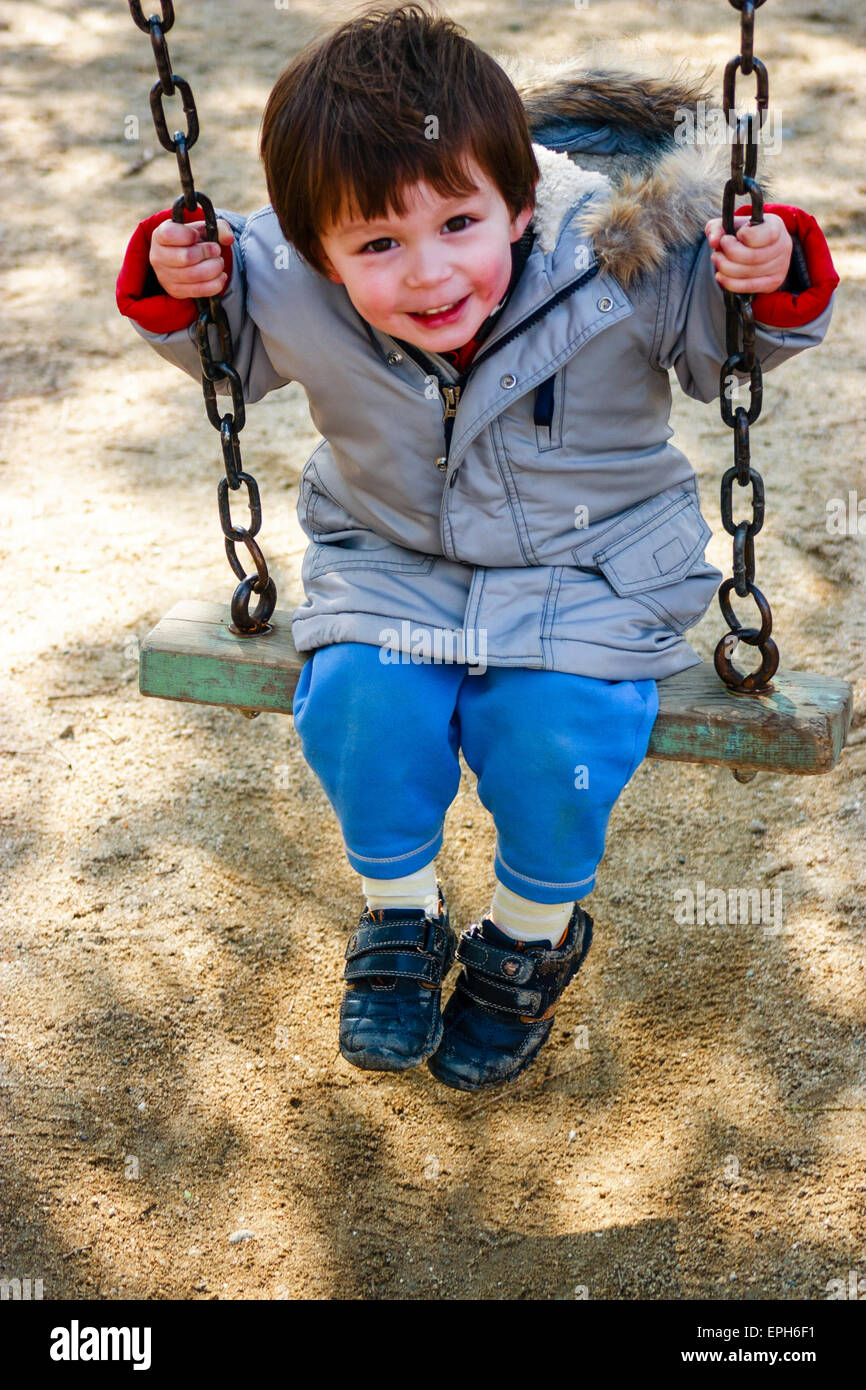 Small Caucasian child, toddler, boy, sitting on swing in coat with red cheeks from the cold, looking up with big - Stock Image
