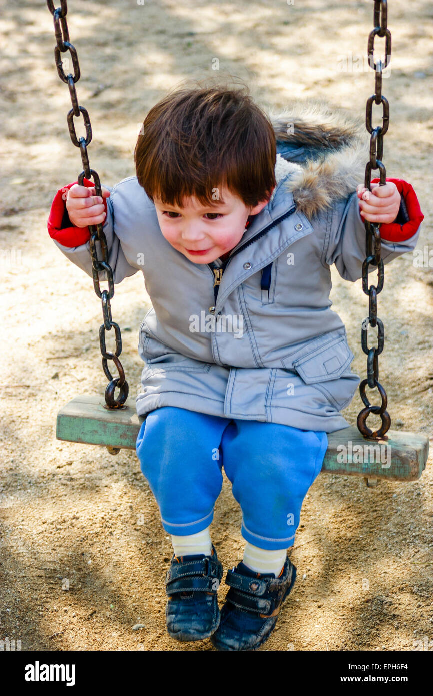 Small Caucasian child, toddler, boy, sitting on swing in coat with red cheeks from the cold, looking ahead - Stock Image