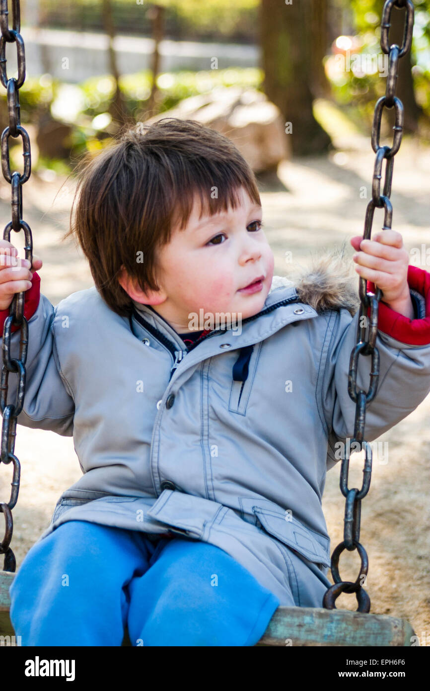 Small Caucasian child, toddler, boy, sitting on swing in coat with red cheeks from the cold, a little soft due to - Stock Image