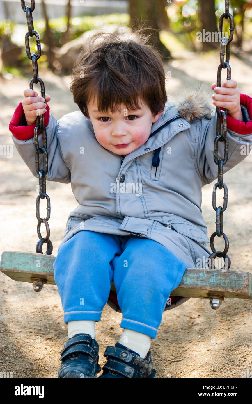 Small Caucasian child, toddler, boy, sitting on swing in coat with red cheeks from the cold, big pleased smile, - Stock Image