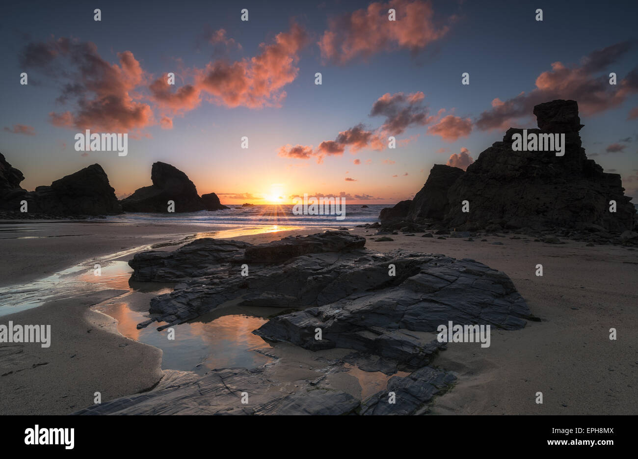 Dramatic sunset at over rock stacks at Porthcothan Bay near Padstow in Cornwall - Stock Image