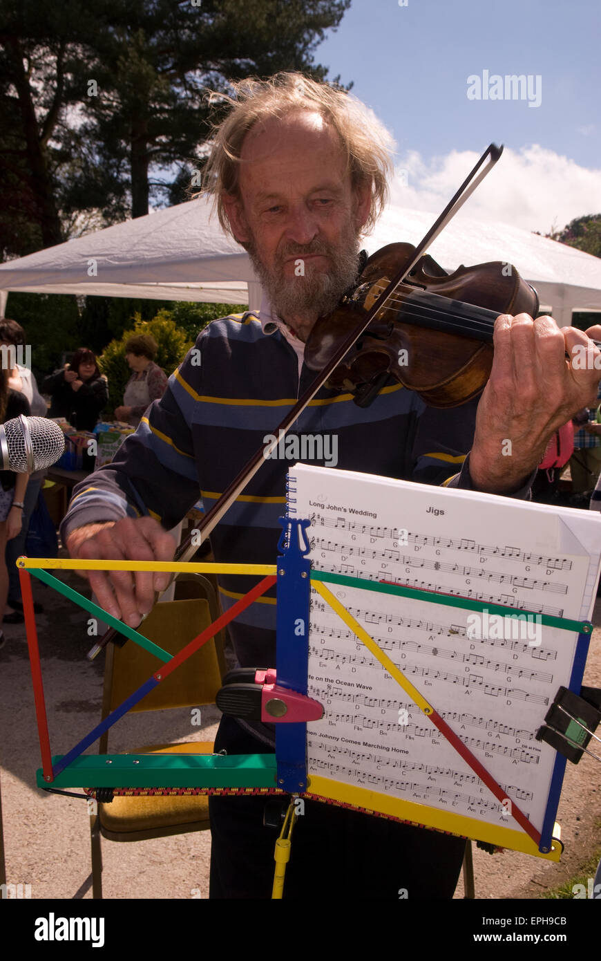 Man entertaining the crowds playing the violin at a May Fayre, Oakhanger, Hampshire, UK. - Stock Image