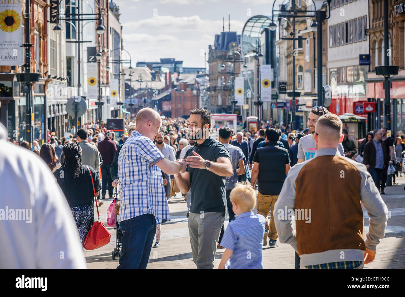 Briggate Busy Shopping District, Leeds, Two Friends Warm Greeting, West Yorkshire - Stock Image