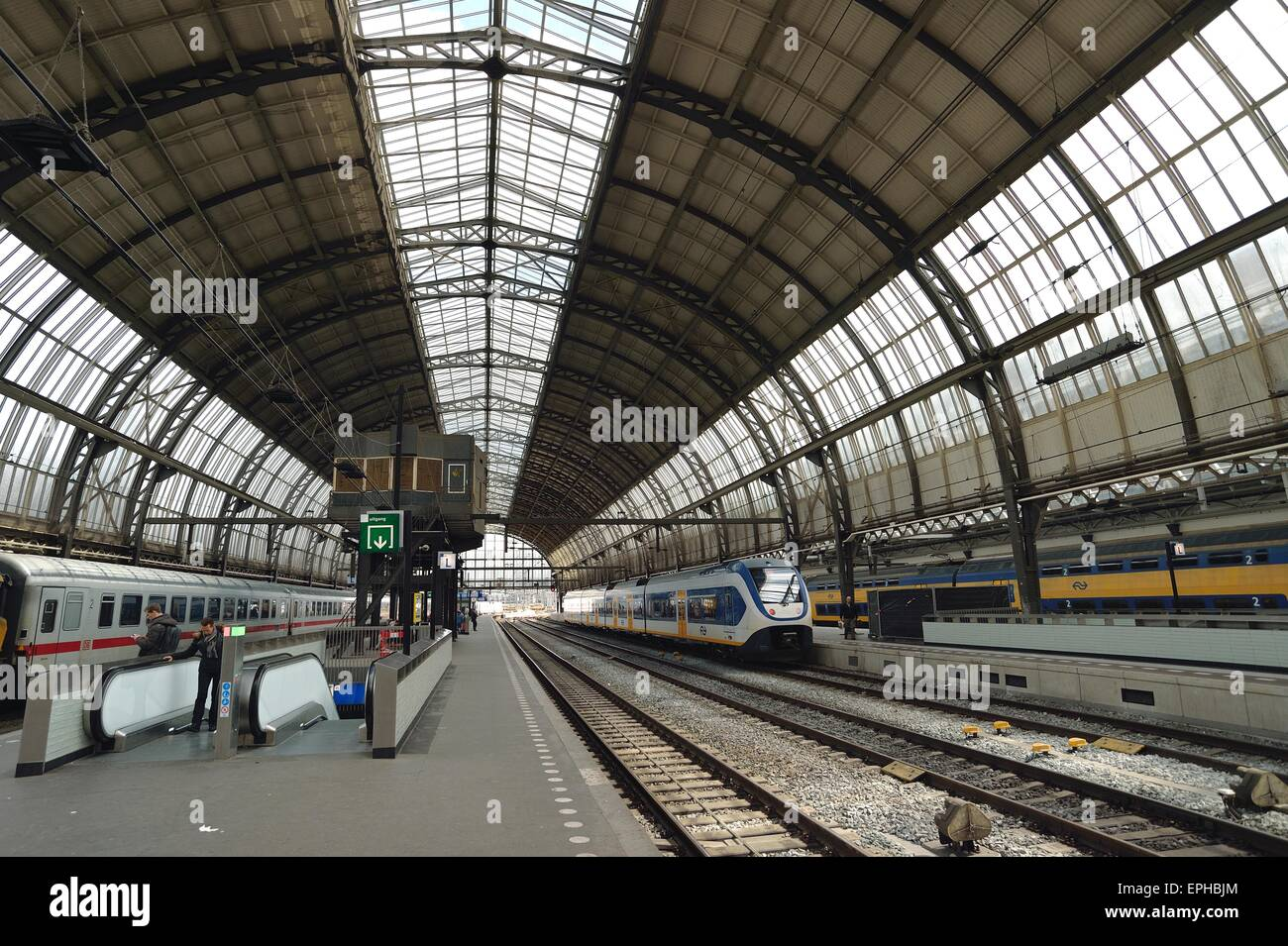 Busy with Trains inside Amsterdam Central Station - Stock Image
