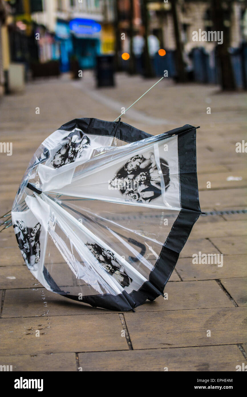 The morning after the night before.  Broken umbrella on the empty streets on a Sunday morning - Stock Image