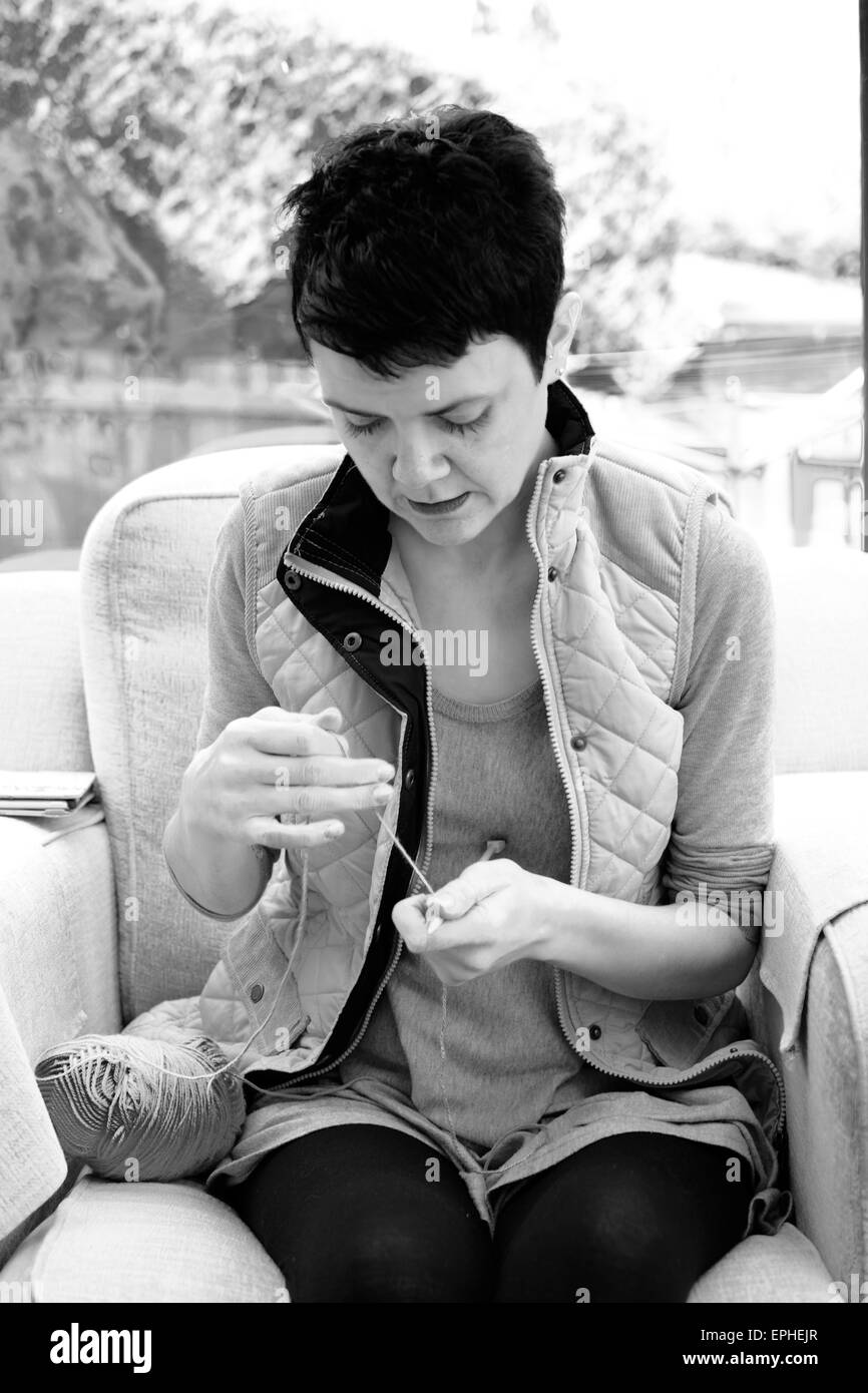 Young woman learning how to knit and taking up a new hobby - Stock Image