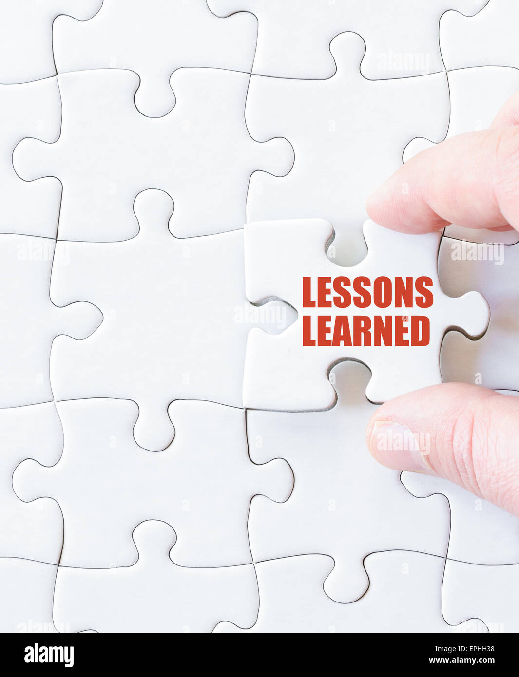 Missing jigsaw puzzle piece with words LESSONS LEARNED. Business concept image for completing the puzzle. - Stock Image